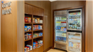 Corner market in the hotel that has various shelves with differnt snacks and two fridges of drinks a