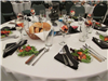 Pre-set tables with place settings and salads and rolls and parfaits in wine glasses