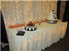 Small lighted cake table with wedding cake and groom cake in the Chisholm Suites