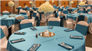 Turquoise and white wedding reception close up of a table setting with white rose center pieces