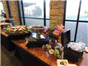 Wedding reception Buffett tables with food and flowers in front of windows