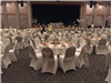 Winter wedding reception with white covered chairs tied with beige tool and napkins