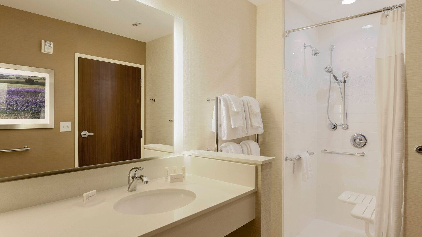 Modern guest bathroom with a large vanity and a roll in shower for easy wheel chair exessability