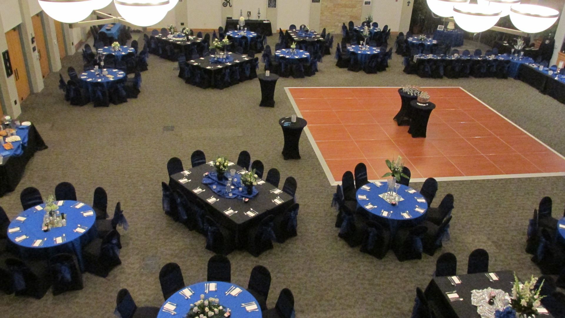 Aerial view of Royal wedding reception of black and blue table settings with dance floor in the midd